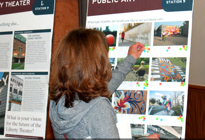Image of resident viewing and labeling poster at community workshop.